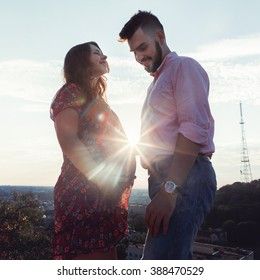 Handsome man & pregnant woman posing at sunrise on cliff, town background
