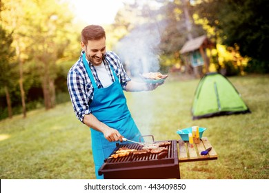 Handsome man preparing barbecue for friends