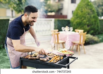 Handsome man preparing barbecue in the yard
