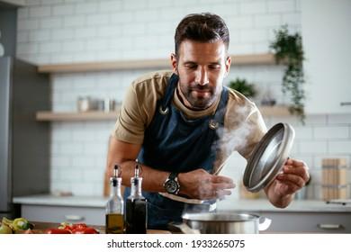 Schöner Mann, der Nudeln in der Küche zubereitet. Guy kocht ein leckeres Essen.