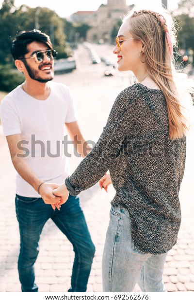 Handsome man and pretty female are holding hands on the street.