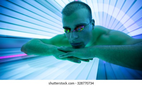 Handsome man with protect glasses in tanning booth