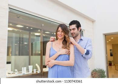 Handsome man putting necklace on his girlfriend neck in front of a jewelry store