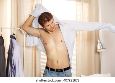 Handsome man putting on shirt standing near window at his room in morning. Preparing for some event or new workday. New opportunities, dating, wedding day or getting ready for job interview concept
