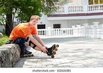 Handsome  man putting on skates going rollerskating in city park