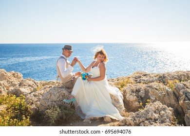 Handsome man putting ring on smiling blonde brides finger at the beach