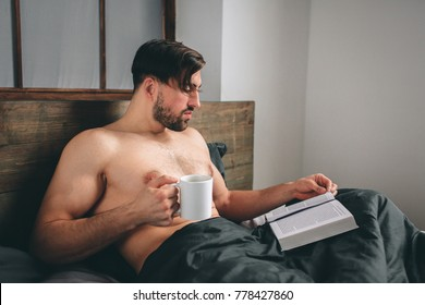 Handsome man reading an exciting book while holding a cup of hot tea or coffee being in his bedroom. It is morning time. Closer view