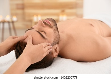 Handsome man receiving face massage in spa salon