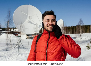 Handsome man in red jacket talking on the cell phone while standing near the radio observatory with big satellite dishes in the forest in winter. Norway