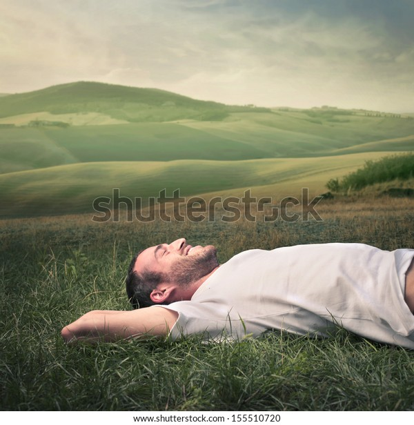 handsome man relaxes lying on the grass in the countryside