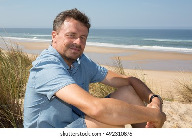 Handsome man relaxing on the beach, sitting on the sand wearing comfortable light clothes