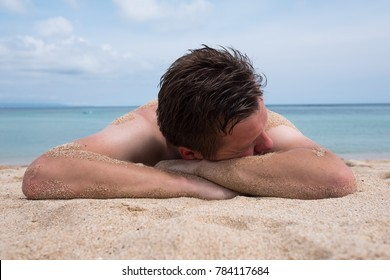 Handsome man relaxing on the beach lying and sleeping on sandy beach