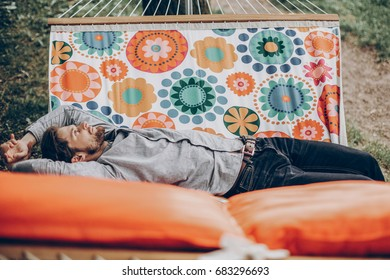 Handsome man relaxing on a hammock on a camping trip, stylish hipster man lying on a hammock thinking and looking at the sky near a lake, relaxation concept