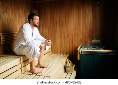 Handsome man relaxing in sauna and staying healthy