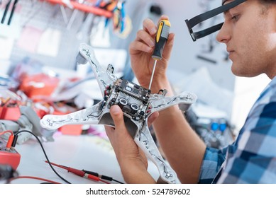 Handsome man repairing drone with screwdriver