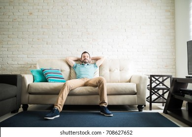 Handsome man resting in a cozy sofa in the living room against a brick wall background with a lot of copy space