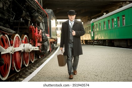 Handsome man in retro suit with suitcase walking on the train platform