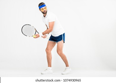handsome man in retro sunglasses playing tennis with racket and ball, isolated on white