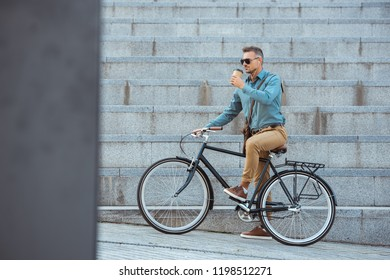 handsome man riding bicycle and drinking from paper cup on street