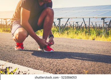 handsome man running on road with solar power plant in morning ;Healthy lifestyle with green energy