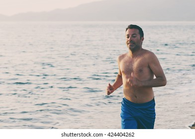 Handsome man running on the sunset beach, selective focus