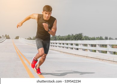 handsome man running and Physical fitness test on bridge ; Healthy lifestyle cardio together at outdoors summer