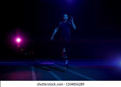 A handsome man runs at night on the athletic track with lights.