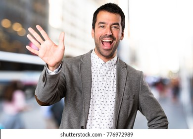 Handsome man saluting on unfocused background