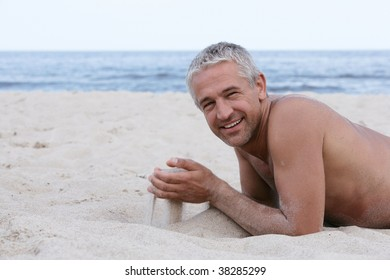 Handsome man with sand in hands lying on the beach