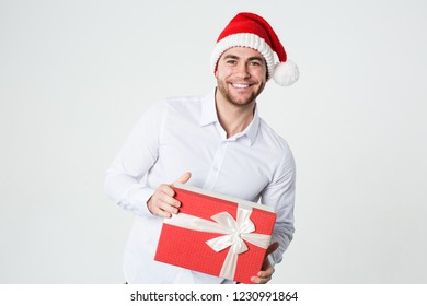 Handsome man in a Santa hat with a gift box in his hands on a white background.