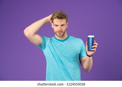 Handsome man with sexy body isolated on purple background. Model with healthy hair holding shampoo bottle, body care and cosmetics concept. Man with trimmed beard stroking his head, hand in hair.