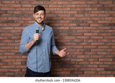 Handsome man in shirt with microphone near brick wall. Space for text