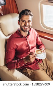 handsome man in shirt smiling and holding cup in private plane