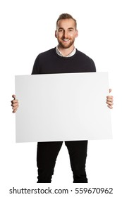 Handsome man in a shirt and sweater standing in front of a white background holding a large blank board, looking at camera smiling.