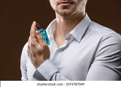 Handsome man in shirt using perfume on dark background, closeup