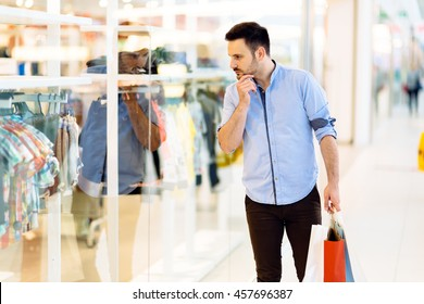 Handsome man shopping clothes in mall