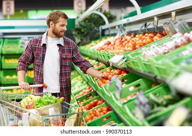 Handsome man with shopping trolley touching tomato in order to define its quality in fruit and vegetable department of supermarket