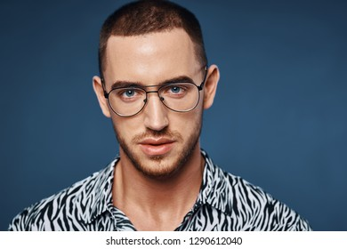 d8a18fda015b Handsome man with short haircut in glasses close-up on a blue background