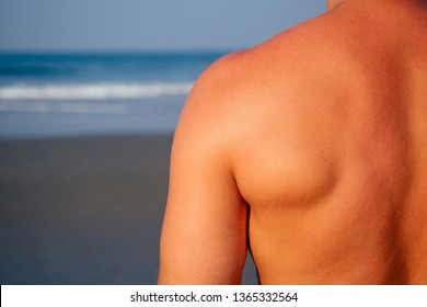 handsome man shoulder closeup applying cream sunscreen lotion on the sea beach.Sexy male model athlete bodybuilder posing the perfect athletic body ,epilation and depilation shugaring concept