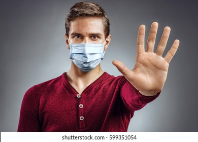 "Handsome man showing gesture ""stop"". Photo of healthy man wears protective mask against infectious diseases and flu. Health care concept."