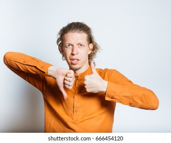 handsome man showing good or bad, up or thumbs down, isolated studio photo on a gray background