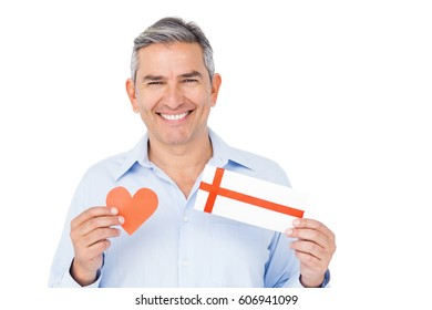 Handsome man showing present and papert heart on white background