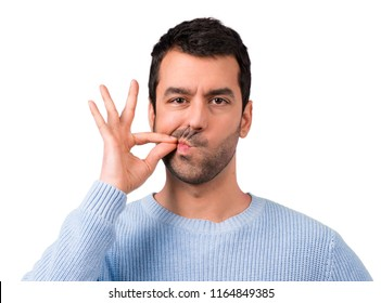 Handsome man showing a sign of closing mouth and silence gesture