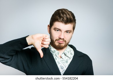 Handsome man showing thumbs down sign to dislike, isolated on background