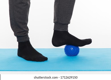 Handsome man shows exercises using the ball with spikes for a myofascial release massage of trigger points. Massage of the foot. Isolated on white.