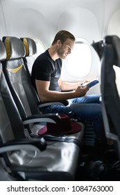 Handsome man sits in the airplane next to the window and reads a magazine. He wears a black T-shirt with blue jeans. There is a crimson hat on a seat near him. Vertical.