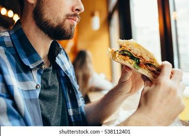 Handsome man sitting in cafe near the window. Young guy has lunch. He is looking at his sandwich and going to eat it immediately