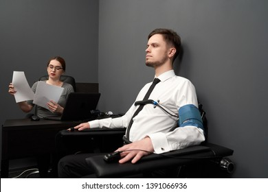 Handsome man sitting in chair in grey room and testing with polygraph. To hands and body attached sensors. Young woman in glasses sitting at table with computer polygraph, looking at papers.