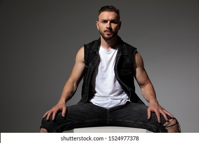 Handsome man sitting with his legs apart while wearing a black jeans vest on gray studio background