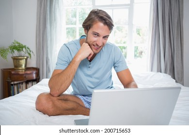 Handsome man sitting on bed using laptop smiling at camera at home in the living room